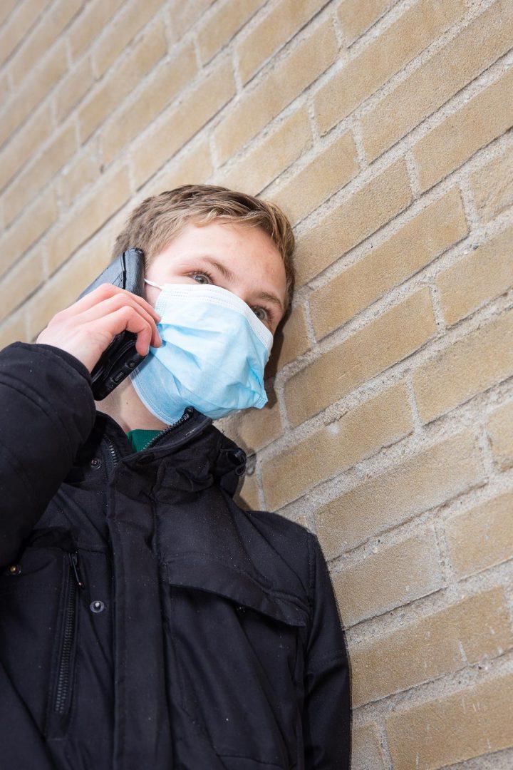 Corona straatfotografie, bellende jongen met mondkapje, portret
