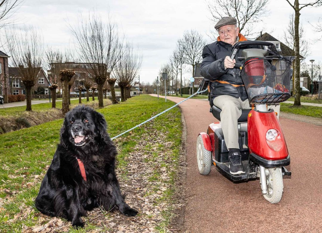 Corona straatfotografie - man laat hond uit in scootmobiel, fotograaf, portretfotograaf