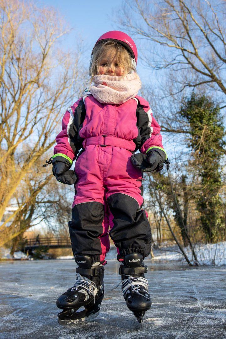 ijspret in Houten, meisje in kleurrijke winterkleding, blozende wangen