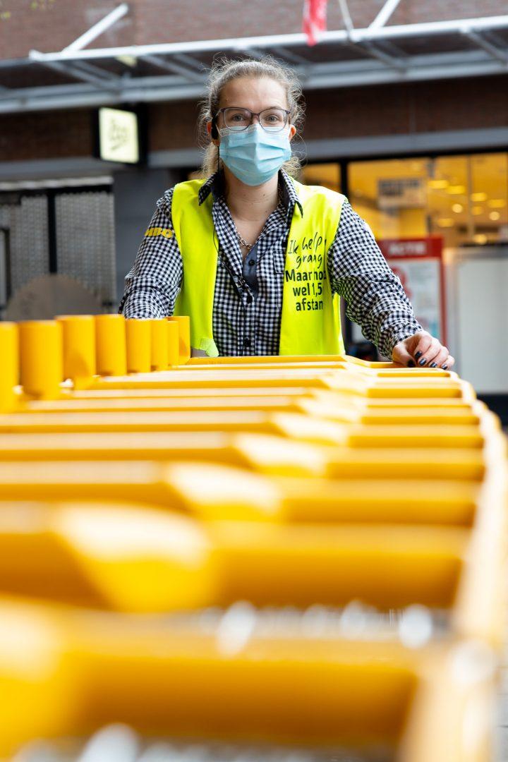 Jumbo medewerkster maakt winkelkarretjes schoon, coronaproof, straatfotografie in Houten,